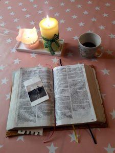 Kuva kahdesta kynttilästä, kahvikupista ja Raamatusta.