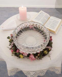 Kuva kastepöydästä, jossa on kynttilä, Raamattu ja kastemalja.