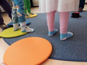 Kuva leikkivien lasten jaloista.